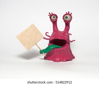 Cobbled together from plasticine funny original monsters. Holds a poster. Isolated character on white background