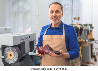 cobbler holding a brand new footwear