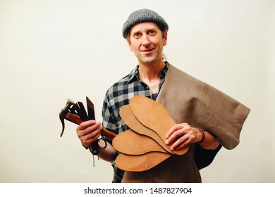 Cobbler holding set of tools and leather. Shoemaker modeling mens shoe at his workshop. Small business concept. Handmade leather shoes.