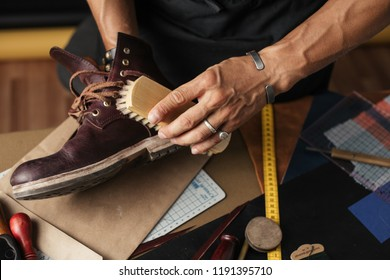 Cobbler s hands cleaning handmade shoes with a brush over his working place background, close up.