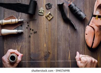 cobbler tools in workshop dark background top view