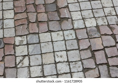 Cobbles close-up. An ancient road lined with a stone in Prague. Texture of smooth stones. Background old stone road in the city. Vintage pattern with natural material