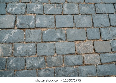Cobbles texture background, old grunge stone blocks floor surface, close up