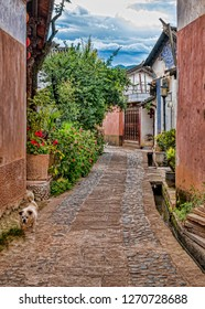 Cobblestone Alley in Historic Chinese Town in Yunnan Province, China. Quaint Street in Small Village with Dog (Shaxi, Yunnan, China).