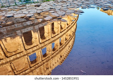 Cobblestone brick paved wet street with Colosseum reflection in Rome, Italy