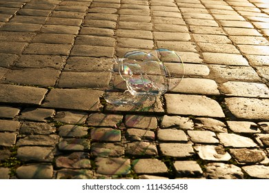 Cobblestone floor with flush light at sunset and soap bubbles