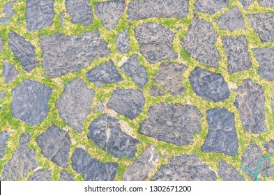 Cobblestone pavement background with copy space. Abstract old close-up cobble stone texture. Paving stone patterned street view from above, paving tiles with grass.