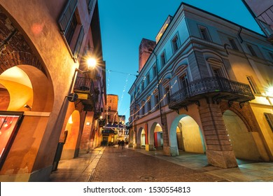 Cobblestone pedestrian street illuminated in evening in Old Town of Alba, Piedmont, Northern Italy (low angle view).