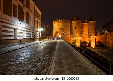 Cobblestone Podwale street and illuminated Barbican at night in city of Warsaw in Poland.