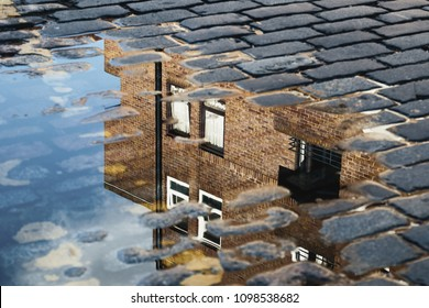 Cobblestone with reflection of house in puddle after rain