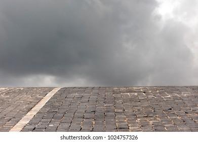 cobblestone road going into the gray sky