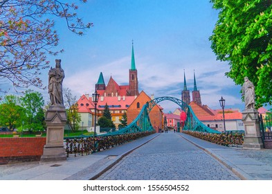 Cobblestone road and Tumski bridge over Odra Oder river, Collegiate Church of Holy Cross and Cathedral of St. John the Baptist in old historical city centre of Wroclaw, evening view, Poland - Shutterstock ID 1556504552
