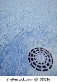 Cobblestone square. Iron hatch. Stone surface