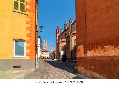 Cobblestone street among colorful walls as medieval towers and Duomo cathedral on background under blues sky in old historic center of Alba, Italy.