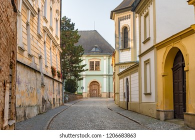 Cobblestone street cityscape with baroque and dilapidated buildings in the old town of Olomouc, Czech Republic.