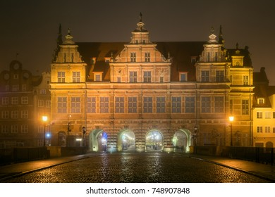 Cobblestone street and historic Green Gate in Old Town of Gdansk in the fog at night. Poland.