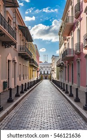 Cobblestone street of old town leading to historic building La Fortaleza at the end of the street