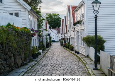 Cobblestone street in the old town of Stavanger, Noway. Traditional white wooden houses with red roofs. Photo taken at the dusk in summer.