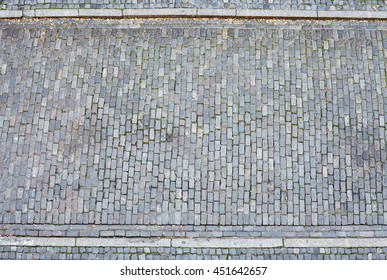 Cobblestone street and pavement from above.