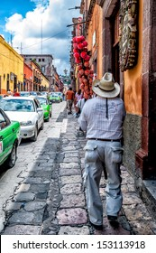 Cobblestone street in the picturesque town of San Miguel de Allende, Mexico. Street vendor carrying pole of candy apples for sale.