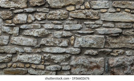 Cobblestone texture.Marble and granite drainage system closeup.Concrete wall with gravel. Gray foundation of the house.