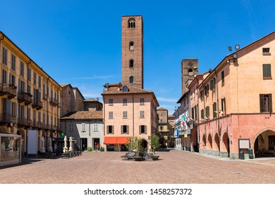 Cobblestone town square surrounded by typical colorful houses and medieval towers in Alba, Piedmont, Northern Italy.