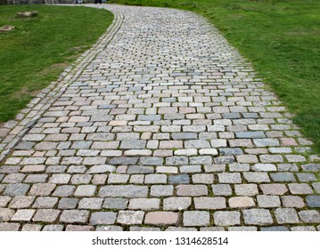 A cobblestone walkway winds off into the distance.
