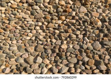 Cobblestone wall texture. Stone pattern. Round cobblestone. Background of stone wall.