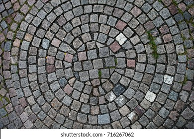 Cobblestones laid out in the shape of a circle seen from above. Perfect to use as a patterned background.