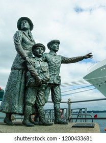COBH, IRELAND – AUGUST 20, 2018: The famous statue of 17-year-old Annie Moore and her brothers looking out onto the harbor commemorates the first immigrants processed at Ellis Island in 1892.