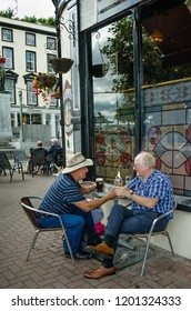 COBH, IRELAND – AUGUST 20, 2018: Two men are enjoying a pint while sitting outside a pub advertising Murphy's Irish Stout beside the town square of one of the country's most important seaports.