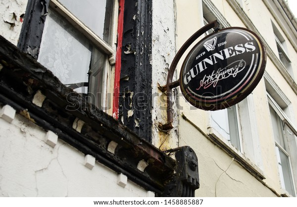Cobh, Ireland - May 31, 2018:  Guinness beer sign on the wall of an old building in Cobh, Ireland