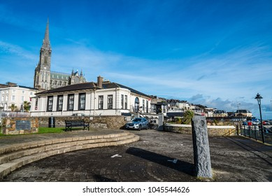 Cobh, Ireland - November 9, 2017: Waterfront and promendade in Cobh with St. Colman Cathedral on background a sunny morning with blue sky. Cobh is a picturesque irish town near Cork