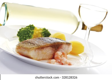 Cobia, fried fish filet, shrimps, brokkoli and potatoes on plate, white wine bottle and glass