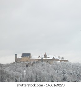 Coburg, Bavaria / Germany - May 15 2019: Snow covered Veste Coburg castle during the winter surrounded with forest.