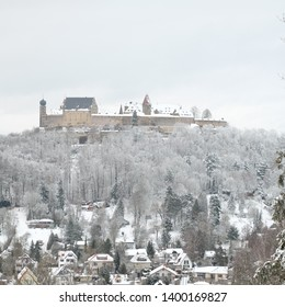 Coburg, Bavaria / Germany - May 15 2019: Snow covered Veste Coburg castle during the winter surrounded with forest and houses.