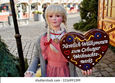 """Coburg, Germany Christmas Market (Weihnachtsmarkt). Mannequin of a traditionally dressed, girl with blonde braids holds a sign that reads in German """"Warm welcome to the Coburg Christmas Market."""""""