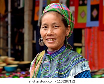 COC LY, VIETNAM - MARCH 20, 2018: Middle-aged Vietnamese Flower H'mong ethnic-minority hill-tribe woman with tribal gold tooth and heavy silver earrings smiles for the camera, on March 20, 2018.