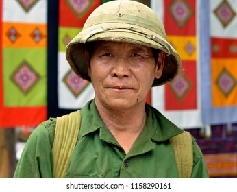 COC LY, VIETNAM - MARCH 20, 2018: Elderly Vietnamese veteran soldier wears a green old military shirt and a well-worn North Vietnam army pith helmet and poses for the camera, on March 201, 2018.