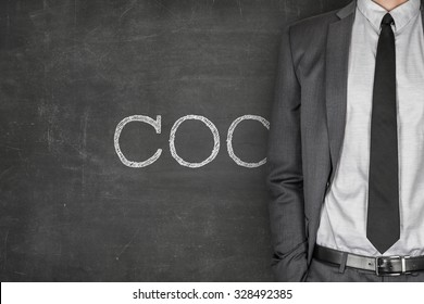 COC on blackboard with businessman in a suit on side