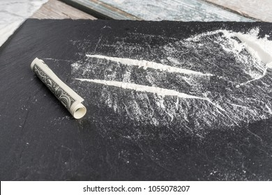 Cocaine divided into paths with bags and roll. Ready to snort