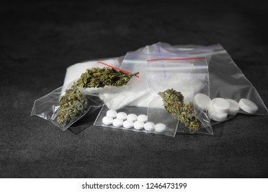 Cocaine, dried hemp and ecstasy on grey table