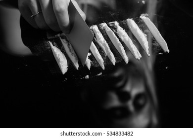 cocaine or other drugs cut with card on mirror with female reflection, hand dividing white powder narcotic, monochrome