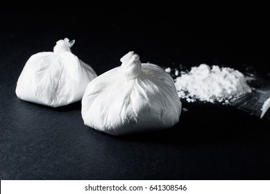 Cocaine poured and cocaine in a bag on a black background