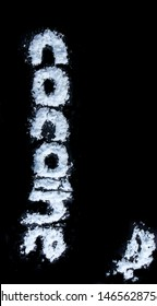 Cocaine spelled with Letters made out of (fake) Cocaine on black Background. With some loose Cocaine in the top right corner.