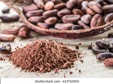 Cocao powder and cocao beans on the wooden table.