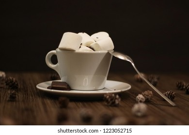 cocao in small coffe cup with marshmallows and chocolate in winter decoration. Winter hot drink on the dark wood table