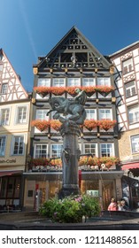 COCHEM, GERMANY, OCTOBER 2018 - St Martin's water fountain in the Market Square with ancient  timber framed buildings in the background, Cochem, Germany
