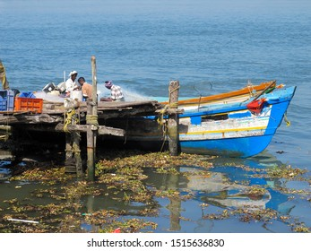 Cochin, India - 3 January 2016 - Men on a fishing boat in Fort Kochi, India on a sunny day.  Image has copy space.