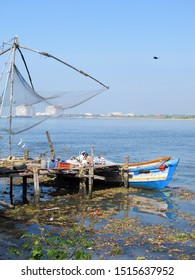 Cochin, India - 3 January 2016 - Men on a fishing boat under a large, traditional fishing net in Fort Kochi, India on a sunny day.  Image has copy space.